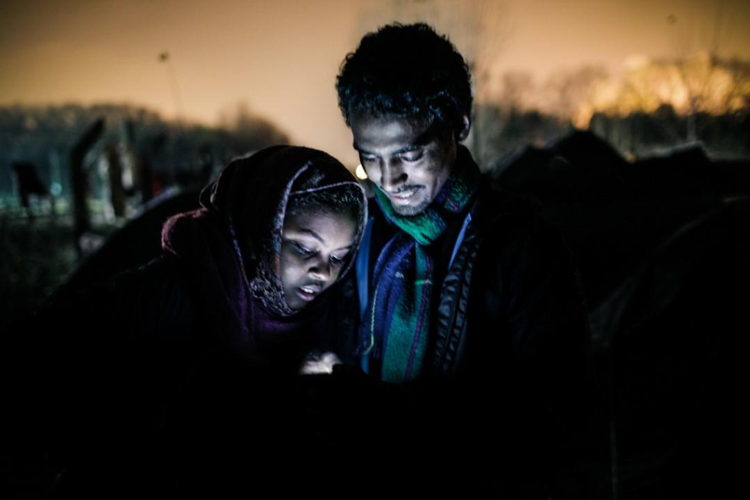 17 Novembre 2014 : Fatiha et Suleyman consultent leurs profils Facebook sur un smartphone prêté par un ami dans le camp communénemt appelé «la Jungle de Tioxide». Calais (62), France.
