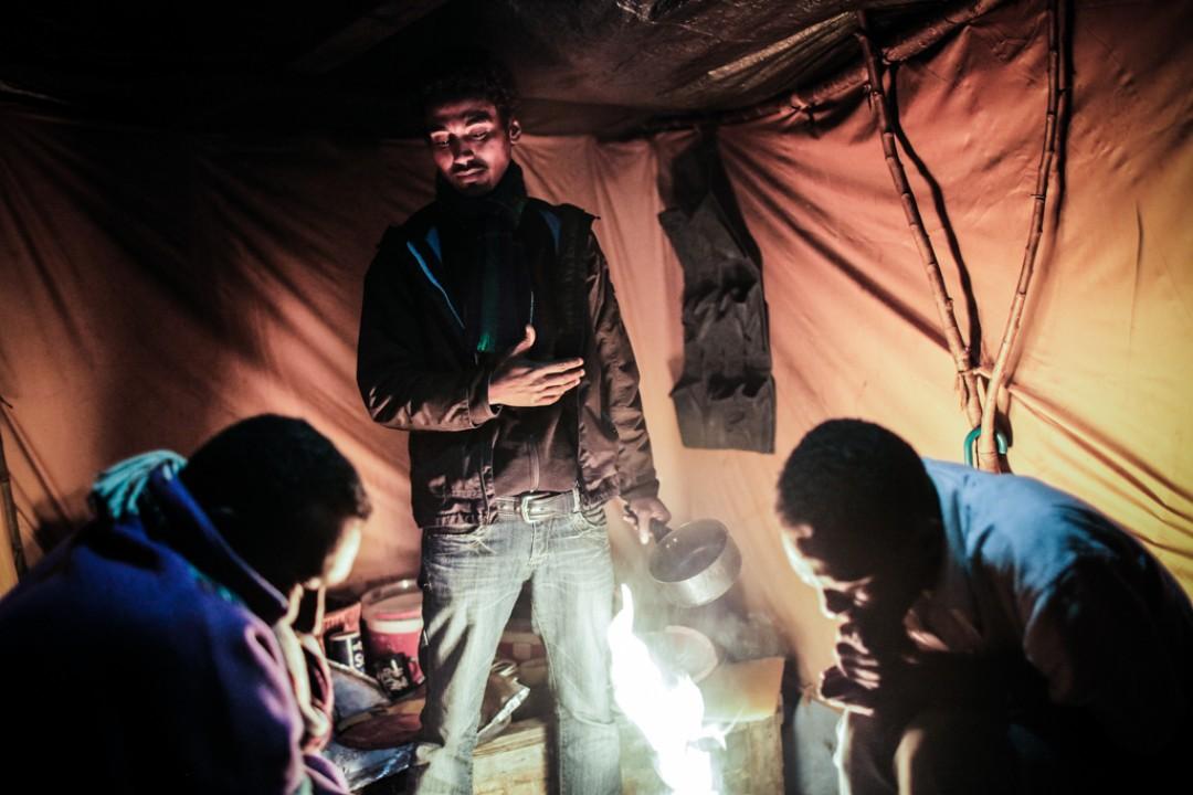 19 Novembre 2014 : La semaine a été très froide, la nuit s'annonce difficile. Suleyman, prépare un thé pendant que Nadir et Abdel jouent aux échecs, dans le camp appelé «la Jungle de Tioxide».Calais (62), France.