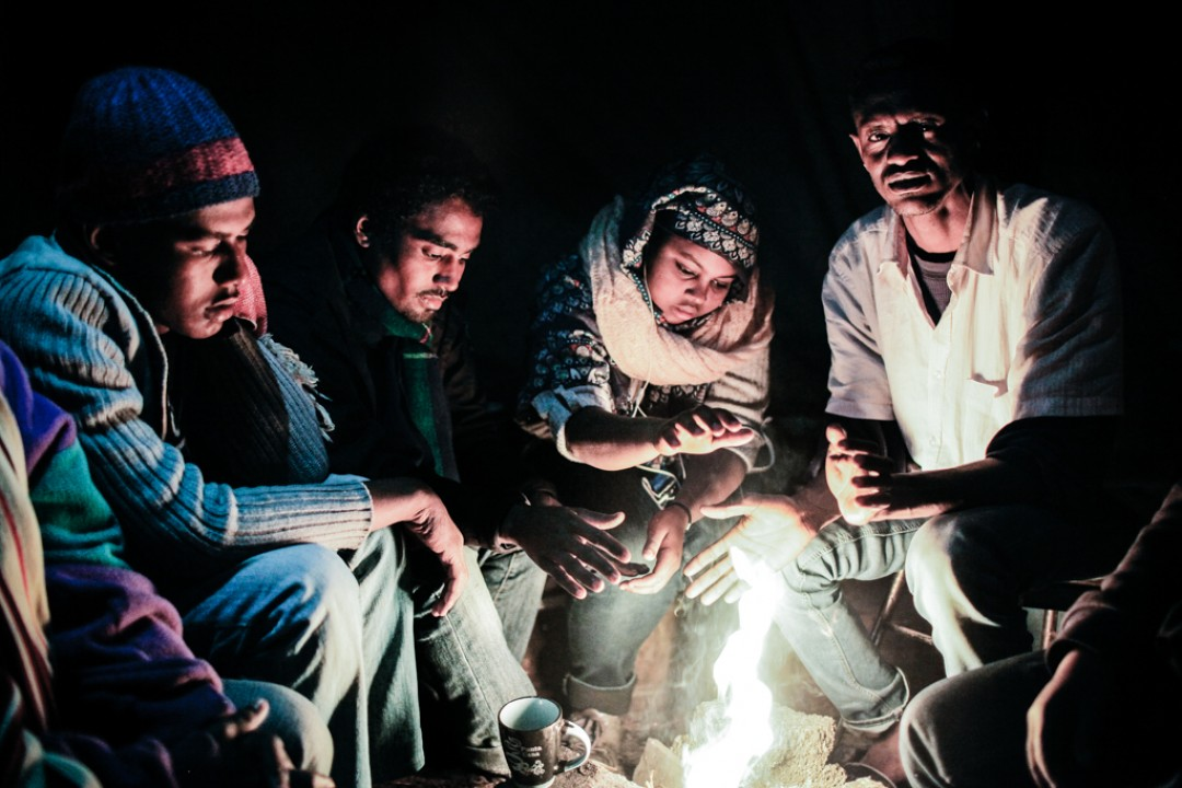 19 Novembre 2014 : Les températures ont chuté depuis le début du mois. Les migrants essayent de se réchauffer près du feu avant d'aller dormir ou de tenter de monter dans un camion. Calais (62), France.