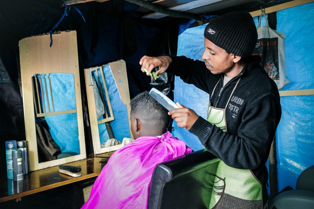 22 Novembre 2014 : Dans un salon informel, le barbier exécute diverses coiffures et tailles de barbe pour quelques euros. Camp appelé «la Jungle de Tioxide», Calais (62), France.