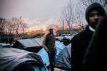 22 Novembre 2014 : Le campement des Soudanais est proche de l'usine TIOXIDE : d'épaisses fumées sont rejetées sur ce site classé SEVESO. Calais (62), France.