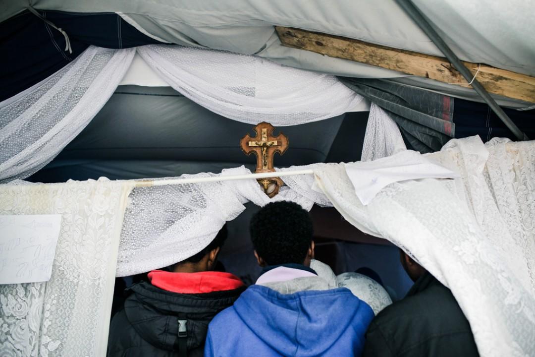 23 Novembre 2014 : Les derniers fidèles se massent devant l'entrée pour communier dans la petite église Orthodoxe dans le camp appelé «la Jungle de Tioxide». Calais (62), France.