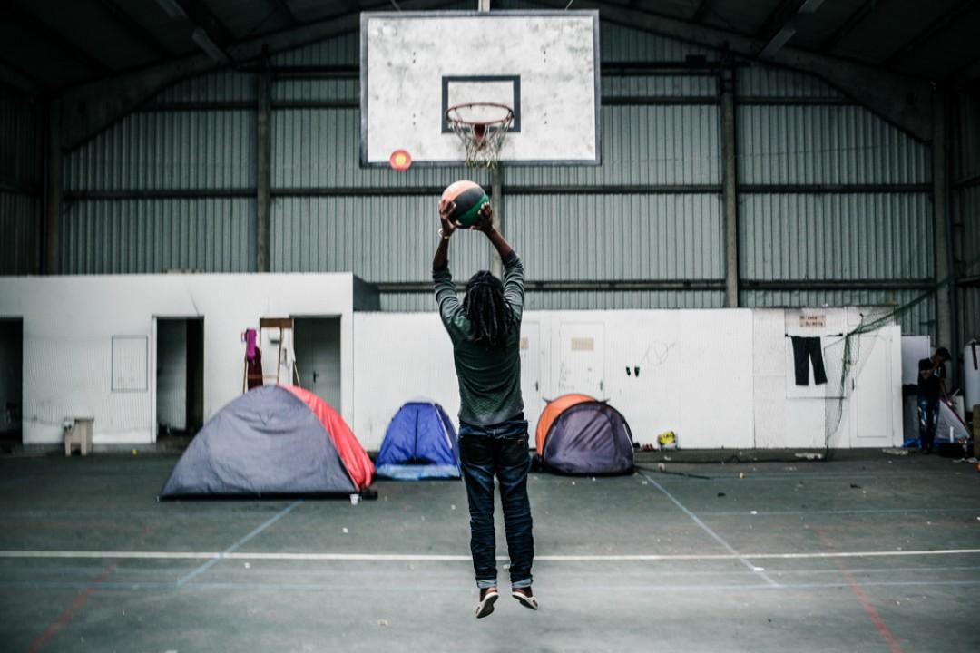 8 Septembre 2014 : Un migrant joue au basket-ball dans le gymnase désaffecté du campement de Tioxide. Depuis Novembre, le gymnase est rempli de tentes. Calais (62), France.