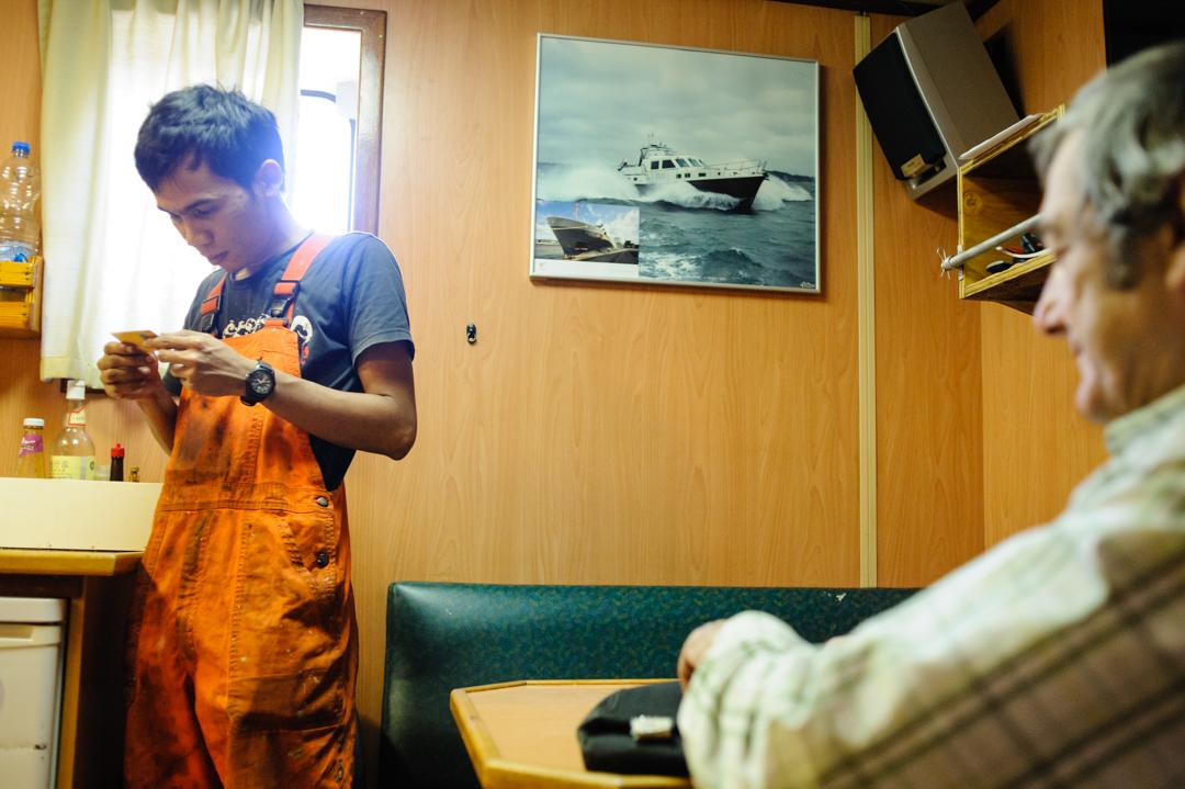 """10 juin 2014 : Un marin vient d'acheter une carte téléphonique internationale au Père Bruno Lery à bord du """"Flinter Sprint"""" au terminal de Arcelor Mital. Le P. Lery est présent dans le cadre de l'accueil des marins proposé par """"La Mission de la Mer"""" à Port de Bouc (13), France.                                                     June 10, 2014: Father Bruno Lery of the Seamen's Club for  """"The Mission of the Sea"""", Port de Bouc (13), France."""