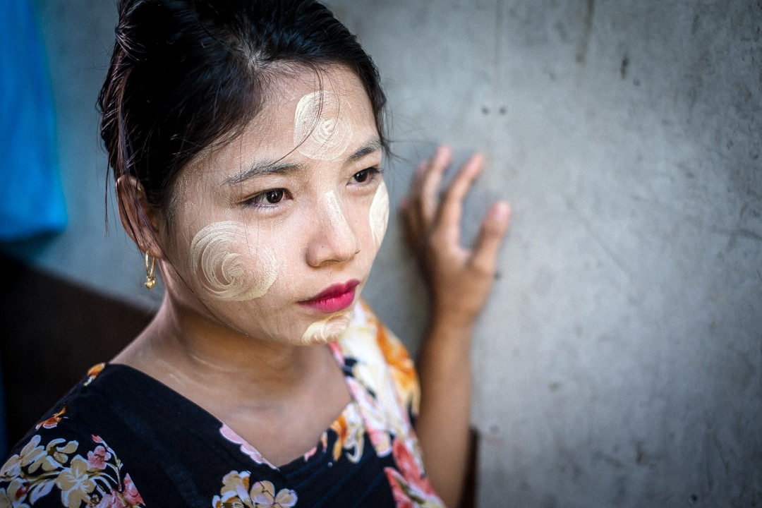 Jeune refugiée birmane dans un bidonville de Phuket, Thaïlande, porteuse de «thanakha», le maquillage typique des birmans. Young Burmese refugee with «thanakha» in a slum of Phuket, Thailand