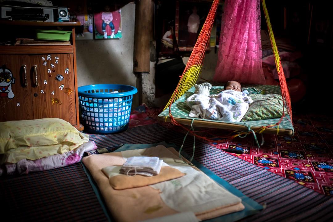 Août 2012 : Un enfant dans une maison du bidonville de la zone portuaire de Phuket, où vivent plusieurs milliers de travailleurs birmans immigrés en situation irrégulière. Thaïlande. August 2012: daily life for burmese refugee, Phuket, Thaïland.
