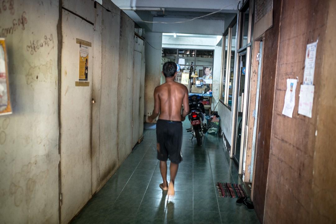 Août 2012 : Un homme marche, dans un appartement communautaire pour travailleurs birmans immigrés en Thaïlande, dans la zone portuaire de Phuket, Thaïlande. August 2012: daily life for burmese refugee, Phuket, Thaïland.