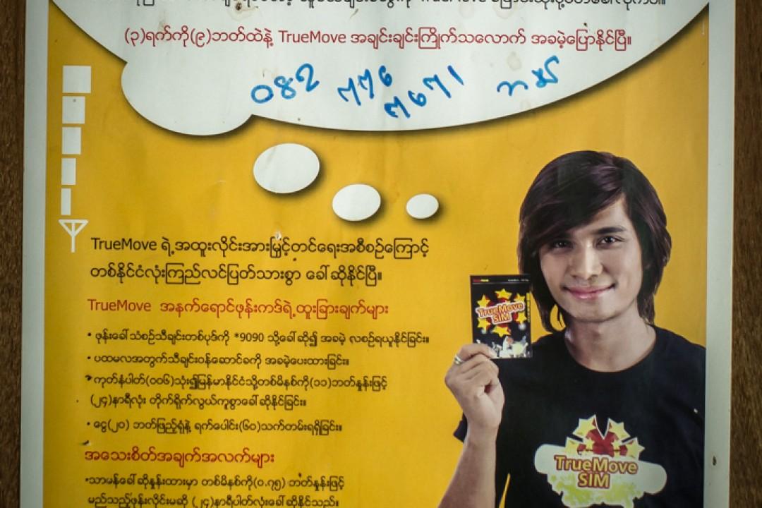 Publicité pour un opérateur de téléphonie mobile thaïlandais, rédigée en birman, dans un appartement communautaire de réfugiés birmans, Phuket, Thaïlande.  August 2012: daily life for burmese refugee, Phuket, Thaïland.