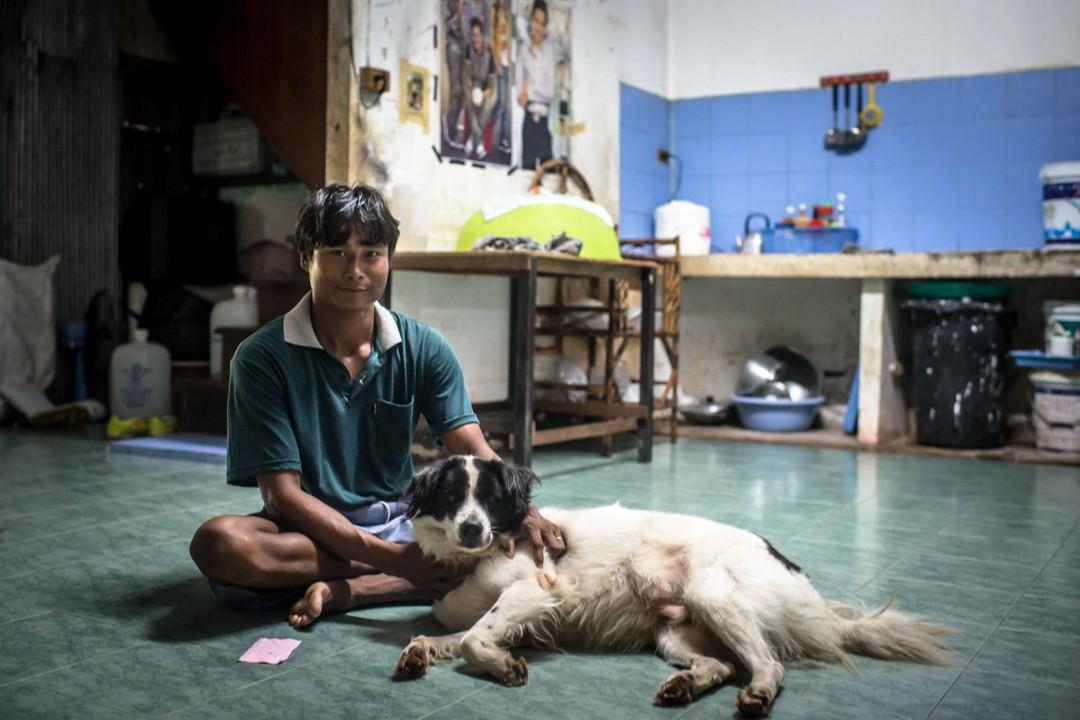 Un réfugié birman et son chien, dans un appartement communautaire de la zone portuaire de Phuket, Thaïlande. August 2012: daily life for burmese refugee, Phuket, Thaïland.