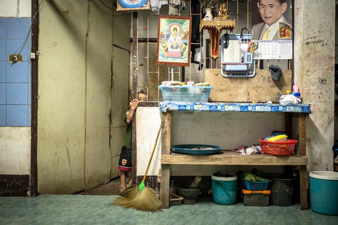 Août 2012 : 7 heures du matin, dans la pièce commune de l'appartement communautaire pour migrants birmans qu'il occupe avec sa famille, Yum Het, 4 ans, joue à cache cache avant de se rendre à l'école informelle montée par sister Lakana, une religieuse de la communauté des soeurs du Bon Pasteur, très impliquée dans l'aide auprès des migrants birmans et soutenue financièrement par l'ONG française Enfants du Mékong. Malgré les difficultés qu'ils rencontrent pour venir s'installer en Thaïlande, les migrants birmans affichent un attachement à la personne du roi de Thaïlande (en portrait en haut à droite de cette photo) étonnant. Phuket, Thaïlande. August 2012: daily life for burmese refugee, Phuket, Thaïland.