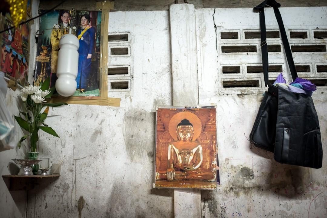 Août 2012 : Un portrait du Bouddha typiquement birman, à côté des portraits du roi et de la reine de Thaïlande – Les migrants birmans affichent tous un portrait du roi chez eux, par soumission, conformisme, respect… Phuket, Thaïlande. August 2012: daily life for burmese refugee, Phuket, Thaïland.